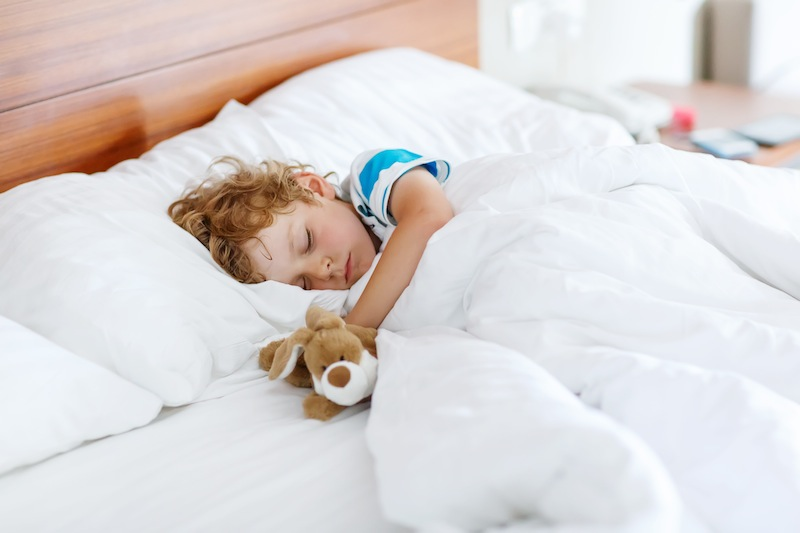 Adorable kid boy sleeping and dreaming in his white bed with toy.